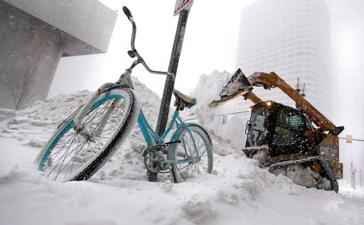 A bicycle is locked to a pole as a loader dumps snow onto a pile while clearing sidewalks in Boston, Thursday, Jan. 4, 2018. Forecasts for the Boston area call for about a foot of snow during the day and blizzard-like conditions. (AP Photo/Charles Krupa)