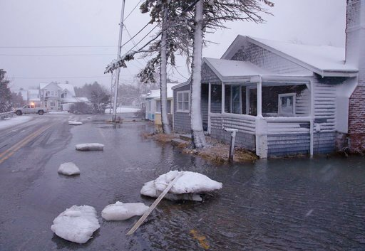 Large chunks of sea ice strewn Ferry Street in front of a flooded house as a utilities truck passes through a nearby intersection Thursday, Jan. 4, 2018, in Marshfield, Mass. (AP Photo/Stephan Savoia)