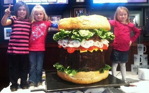 """In a Thursday, Oct. 20, 2011 photo provided by Mallie's Sports Grill in Southgate, Mich., children stand next to a 338-pound """"Absulutely Ridiculous Burger"""" at the sports bar."""