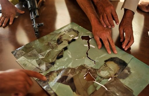 Libyan revolutionary fighters show a picture of Cuban leader Fidel Castro and a Libya's ousted leader Moammar Gadhafi in a house belonging to Gadhafi near Sirte, Libya, Tuesday, Sept. 27, 2011.
