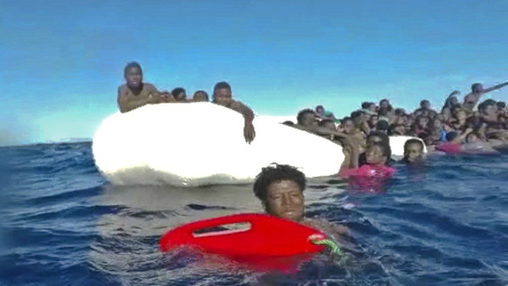 This frame of a video taken by the Italian Coast Guard on Jan. 6, 2018, in the Mediterranean Sea off Libya, shows migrants being rescued from dinghies as they try to cross to Italy.  (Italian Coast Guard via AP Photo)