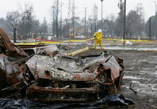 With a burned car in the foreground a worker finishes up erosion control efforts in the wildfire damaged Coffey Park neighborhood, Monday, Jan. 8, 2018, in Santa Rosa, Calif. (AP Photo/Eric Risberg)