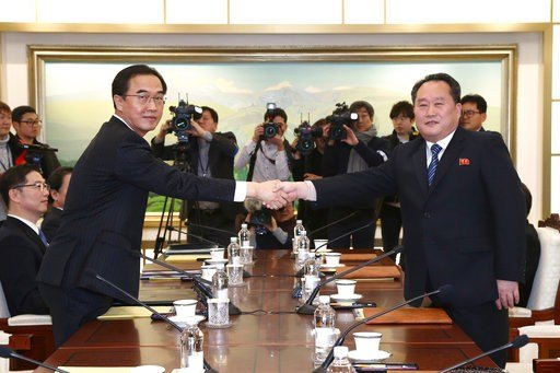 South Korean Unification Minister Cho Myoung-gyon, left, poses with head of North Korean delegation Ri Son Gwon while shaking hands during their meeting at the Panmunjom in the Demilitarized Zone in Paju, South Korea, Tuesday, Jan. 9, 2018