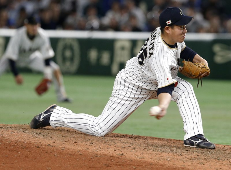 In this March 15, 2017, file photo, Japan's closer Kazuhisa Makita pitches against Israel during the ninth inning of their second round game of the World Baseball Classic at Tokyo Dome in Tokyo.
