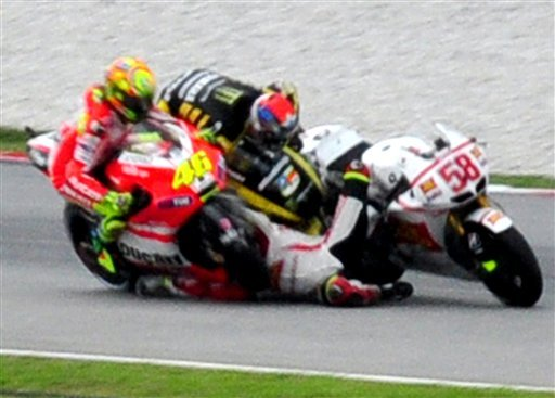 Crash between Colin Edwards, center, Valentino Rossi from Italy, left, and Marco Simoncelli from Italy is seen at turn 11 during the Malaysian MotoGP Grand Prix in Sepang, Malaysia, Sunday, Oct. 23, 2011. (AP)
