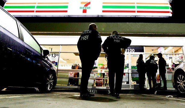 U.S. Immigration and Customs Enforcement agents serve an employment audit notice at a 7-Eleven in Los Angeles.