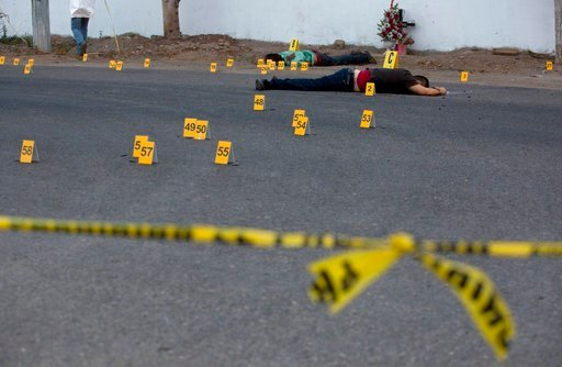 FILE - In this June 29, 2017 file photo, investigators mark the spot where spent bullet casing fell next several bodies lying on a road in the town of Navolato, Sinaloa state, Mexico.(AP Photo/Enric Marti, File)