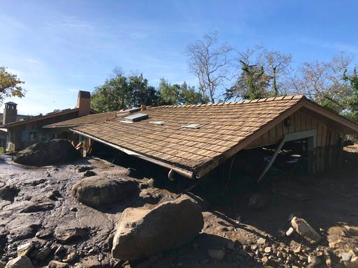 In this photo provided by Santa Barbara County Fire Department, mudflow, boulders, and debris from heavy rain runoff from early Tuesday reached the roof of a single story home in Montecito, Calif., on Wednesday, Jan. 10, 2018.