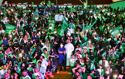In this Sept. 23, 2017 file photo released by Saudi Press Agency, SPA, Saudi men and women attend national day ceremonies at the King Fahd stadium in Riyadh, Saudi Arabia.