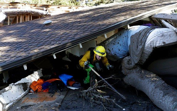 Colette Layton, bottom, of the Atascadero Fire Dept, searches a home Saturday, Jan. 13, 2018, in Montecito, Calif.