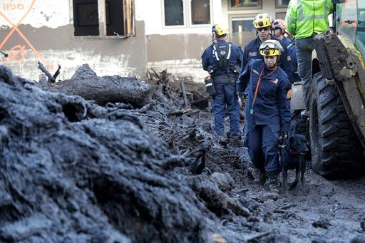 Rescue workers slogged through knee-deep ooze and used long poles to probe for bodies Thursday as the search dragged on for victims of the mudslides that slammed this wealthy coastal town. (AP Photo/Marcio Jose Sanchez)