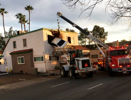 Authorities say the Nissan Altima hit a center divider early Sunday, soared into the air and plowed into the top floor of the two-story structure. (Capt. Stephen Horner /Orange County Fire Authority via AP)