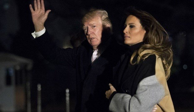 President Donald Trump with first lady Melania Trump waves as he returns to the White House.