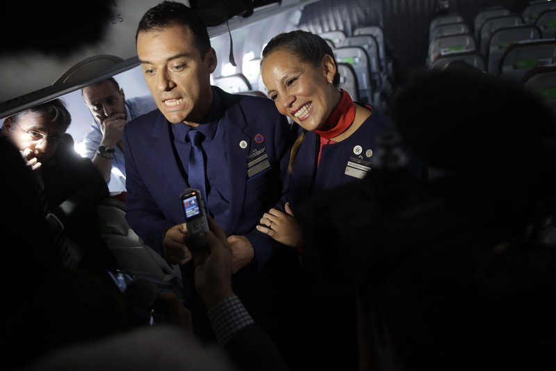 Flight attendants Carlos Ciuffardi, left, and Paola Podest, talk with journalists during a flight from Santiago, Chile, to Iquique, Chile, after Pope Francis married them in-flight early Thursday, Jan. 18, 2018.