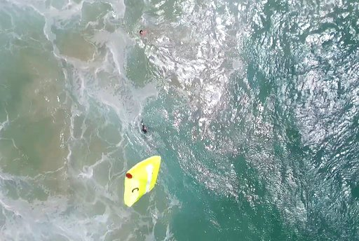 In this Thursday, Jan. 18, 2018 image made from a video provided by Westpac Little Ripper, a yellow flotation device is dropped from a flying drone toward two teenagers caught in a riptide in heavy seas off the Australian coast. (Westpac Little Ripper via