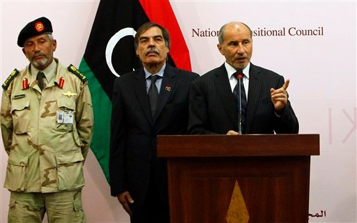 Libyan Transitional National Council chairman Mustafa Abdul-Jalil, right, and Ali Tarhouni, Libyan National Transitional Council's minister for Oil and Finance, second left, greet Libyan veterans during a press conference in Benghazi, Libya, (AP)