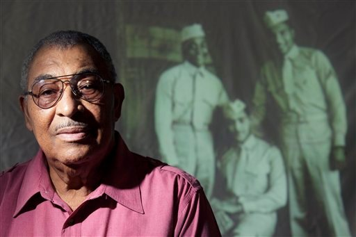 In this photo taken Wednesday, Oct. 5, 2011, Carrel Reavis poses for a portrait in front of an image of him, far right, with two friends taken in the late 1940s in San Diego.