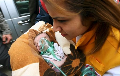 A Turkish medical doctor carries Azra Karaduman, a two-week-old baby girl saved by Turkish rescuers who continue to work to save people trapped under debris of a collapsed building in Ercis, Van, eastern Turkey, Tuesday, Oct. 25, 2011. (AP)