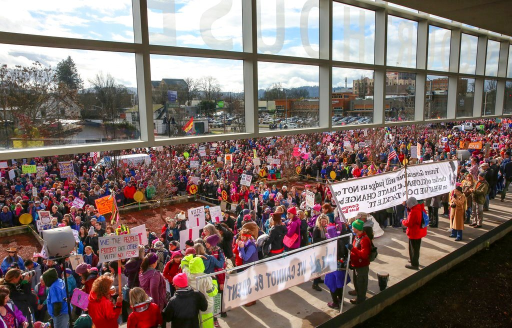 Protesters gather at the federal courthouse in downtown Eugene, Ore., for the Women's March calling attention to equal rights and equality for women on Saturday, Jan. 20, 2018. (Collin Andrew/The Register-Guard via AP)