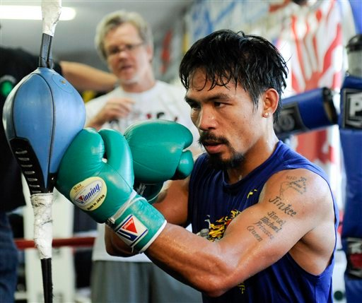 In this photo made Oct. 20, 2011, boxer Manny Pacquiao works out as trainer Freddie Roach looks on at the Wild Card Boxing Club in the Hollywood section of Los Angeles.