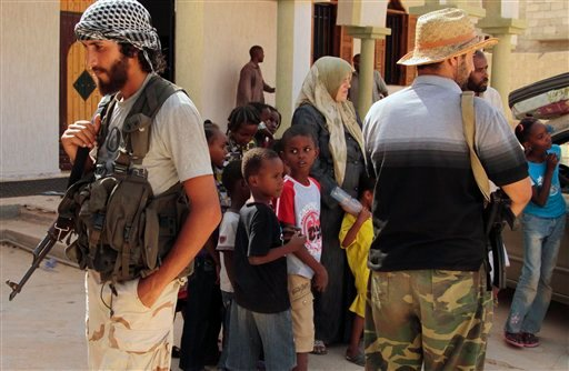 Children and families are seen stranded outside a mosque guarded by revolutionary fighters in Sirte, Libya, Monday, Sep. 26, 2011.