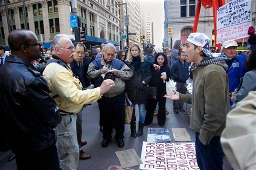 An exchange of opinions between a supporter of the Occupy Wall Street protests, right, and passersby attracts attention at Zuccotti Park in New York on Tuesday, Oct. 25, 2011.  (AP Photo/Bebeto Matthews)