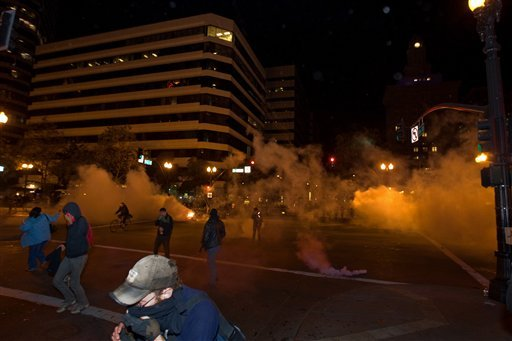 Occupy Wall Street protesters run from tear gas deployed by police at 14th Street and Broadway in Oakland, Calif., Tuesday, Oct. 25, 2011. (AP Photo/Darryl Bush)