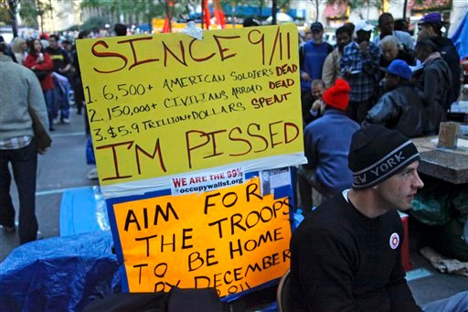 A protester post a sign about the cost of war, reflecting the range of issues found among participants of the Occupy Wall Street protest at Zuccotti Park, Tuesday, Oct. 25, 2011 in New York. (AP Photo/Bebeto Matthews)