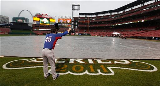 Texas Rangers' Derek Holland yells across a covered infield at Busch Stadium Wednesday, Oct. 26, 2011, in St. Louis, after officials announced that Game 6 of baseball's World Series is postponed due to rain. (AP Photo/Paul Sancya)