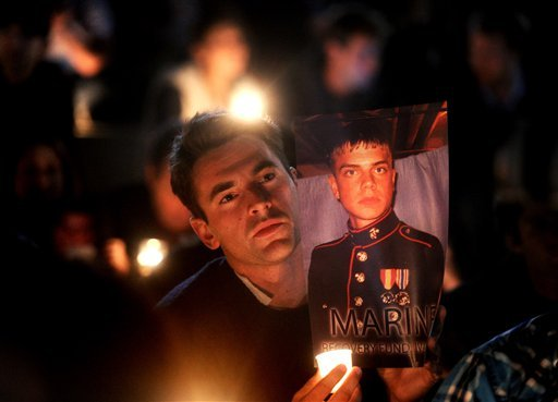 Greg Reft holds a photo of Scott Olsen during a candlelight vigil on Thursday, Oct. 27, 2011, in Oakland, Calif. (AP)