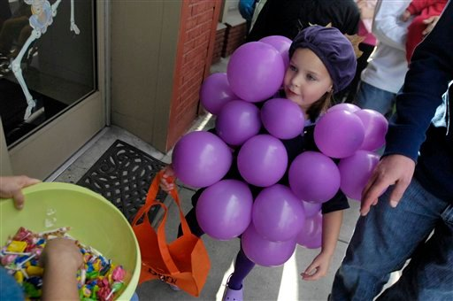 FILE - In this Friday, Oct. 29, 2010 file photo, Hannah Moos, 5, dressed as a bunch of grapes, asks for candy with her father Kyle, of Melba, Idaho at a Halloween event in downtown Nampa, Idaho.