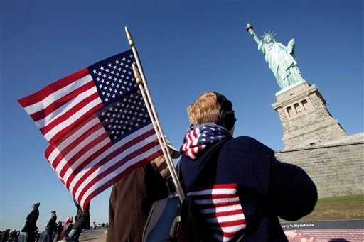 Donna Bodkins, of Fisher, West Virginia, caries American flags while visiting the Statue of Liberty to mark her 125th anniversary, Friday, Oct. 28, 2011 in New York.