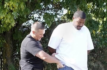 Parole Agent Clint Cooley checks the pockets of parolee Kevin Carlock, a transient registered sex-offender in Sacramento, Calif., Friday, Oct. 28, 2011.