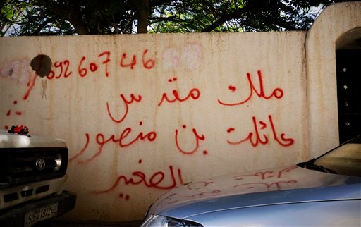 """In this Thursday, Oct. 27, 2011 photo, graffiti on the wall of a house reads in Arabic, """"house of bin Mansour,"""" in Tripoli, Libya."""