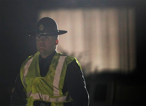 A Kansas State Trooper stands his post near the Bartlett Grain Co. elevator in Atchison, Kan., Saturday, Oct. 29, 2011. An explosion at the grain elevator injured at least two people. (AP Photo/Orlin Wagner)
