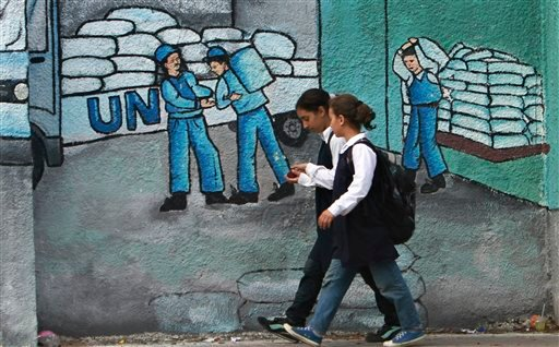Palestinian school girls walk past a graffiti on a wall depicting UN humanitarian aid supplies, in Gaza City, Monday, Oct. 31, 2011. (AP)