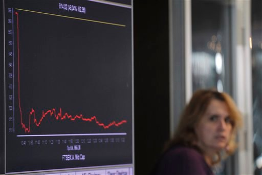 A woman passes a screen showing a graph of falling stocks at the Athens Stock Exchange, in Athens, on Tuesday, Nov. 1, 2011. (AP)