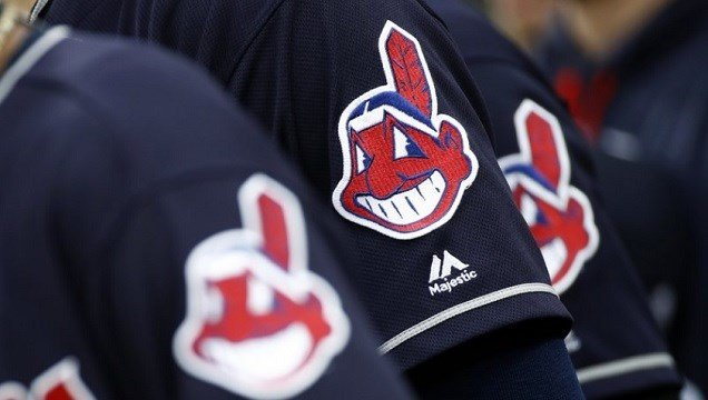 Cleveland Indians wear uniforms featuring mascot Chief Wahoo as they stand on the field for the national anthem.