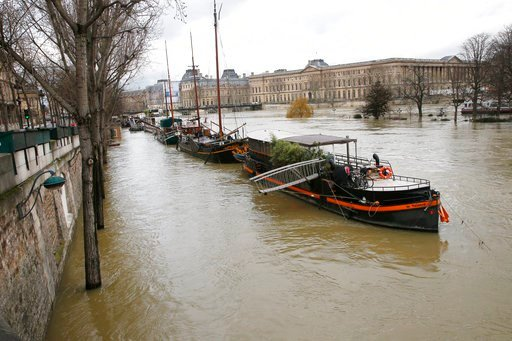 Boats are lined up along the flooded river Seine in Paris, France, Monday, Jan. 29, 2018. Floodwaters have reached a peak in Paris and are now threatening towns downstream along the rain-engorged Seine River. (AP Photo/Michel Euler)