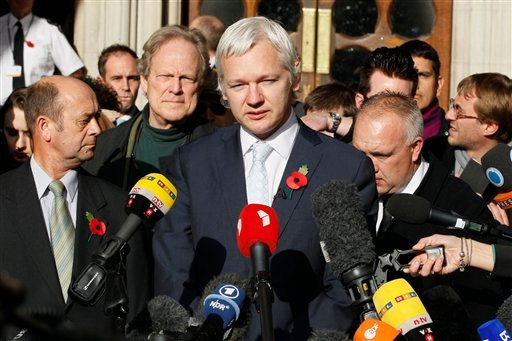 The founder of WikiLeaks Julian Assange, center, gives a statement to the media after his extradition hearing at the High Court in London, Wednesday, Nov. 2, 2011. (AP Photo/Kirsty Wigglesworth)