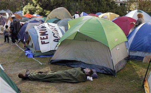 A protester sleeps under a blanket at the Occupy Oakland encampment Tuesday, Nov. 1, 2011, in Oakland, Calif. (AP Photo/Ben Margot)