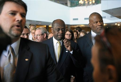 Republican presidential candidate Herman Cain, center, is surrounded by security and staff as he walks through a hotel lobby in Alexandria, Va., Wednesday, Nov. 2, 2011, before speaking after meeting with doctors attending the Docs4PatientCare conference.
