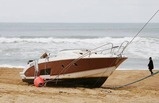 The speedboat belonging to sportswear maker Quiksilver CEO Pierre Agnes lays ashore on the beach of Hossegor, southwestern France, Tuesday, Jan. 30 2018.