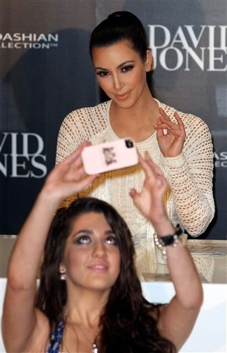 A fan takes a self portrait with celebrity Kim Kardashian behind during a launch of her fashion accessory range at a department store in Sydney, Australia, Thursday, Nov. 3, 2011. (AP Photo/Rob Griffith)