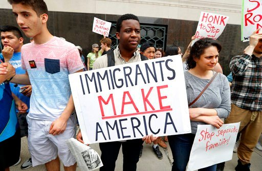 FILE - In this Tuesday, May 16, 2017, file photo, Torianto Johnson, a freshman at Pioneer High School in Ann Arbor, holds a sign supporting immigrants during a rally outside a federal courthouse in Detroit. (AP Photo/Paul Sancya, File)