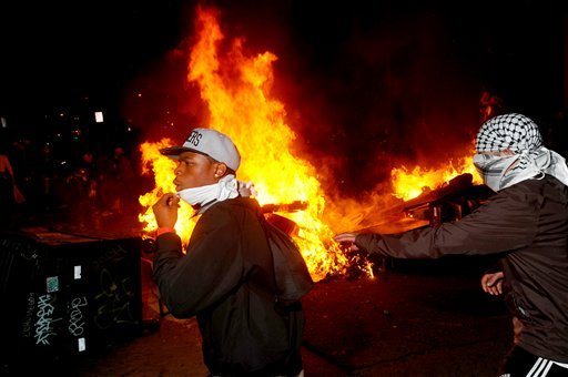 Occupy Oakland protesters pass a burning garbage heap during a confrontation with police on Thursday, Nov. 3, 2011, in Oakland, Calif. (AP Photo/Noah Berger)