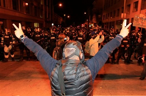 An Occupy protester shows peace signs to Oakland Police officers in Oakland, Calif., Thursday, Nov. 3, 2011. (AP Photo/Jeff Chiu)