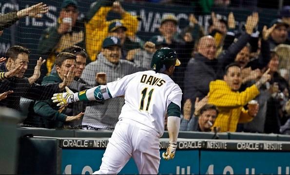Oakland Athletics' Rajai Davis celebrates with fans as he scores.