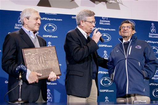 Penn State President Graham Spanier, left, and Athletic Director Tim Curley, center, present head football coach Joe Paterno with a plague commemorating his 409th collegiate win after an NCAA college football game against Illinois in State College, Pa.