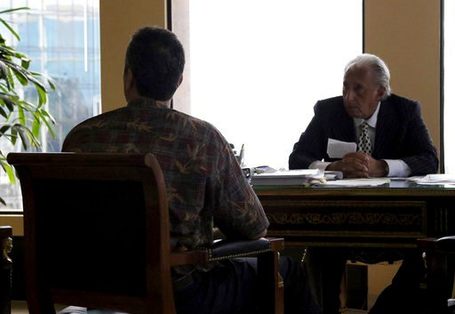 Honolulu attorney Michael Green, right, sits with his client, the former Hawaii Emergency Management Agency employee who sent a false missile alert to residents and visitors in Hawaii, left, during an interview with reporters, Friday, Feb. 2, 2018 in Hono
